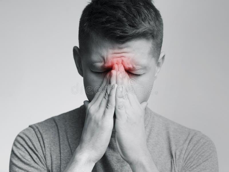 Droevige mens die zijn neus houden omdat sinuspijn stock fotografie