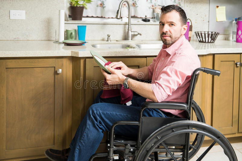 Droevige mens op de schotels van de rolstoelwas royalty-vrije stock foto's