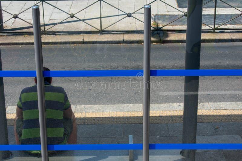 Droevige mensenzitting bij blauwe gestripte bushalte op zonnige dag royalty-vrije stock fotografie