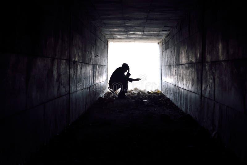 Droevige mensenzitting in de tunnel royalty-vrije stock afbeelding