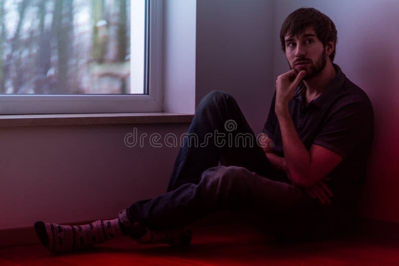 Droevige mensenzitting door het venster stock afbeelding
