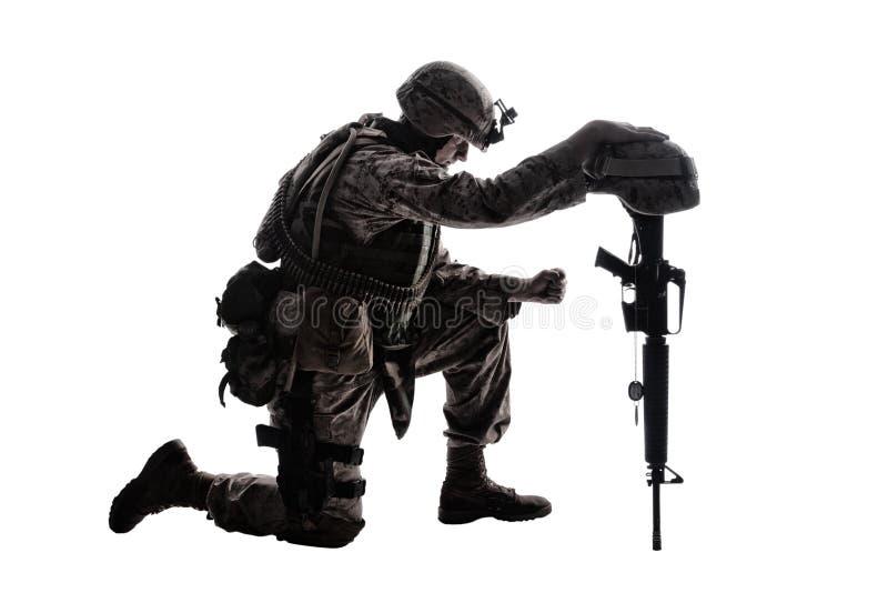 Droevige militair die wegens vriendendood knielen stock foto's