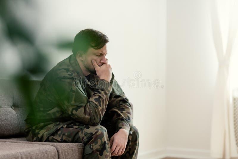 Droevige militair in eenvormig behandelend zijn mond terwijl het zitten op een bank stock afbeelding