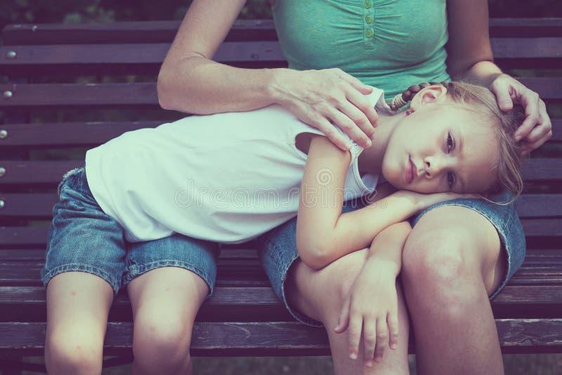 Droevige moeder en dochterzitting op bank in het park stock foto's