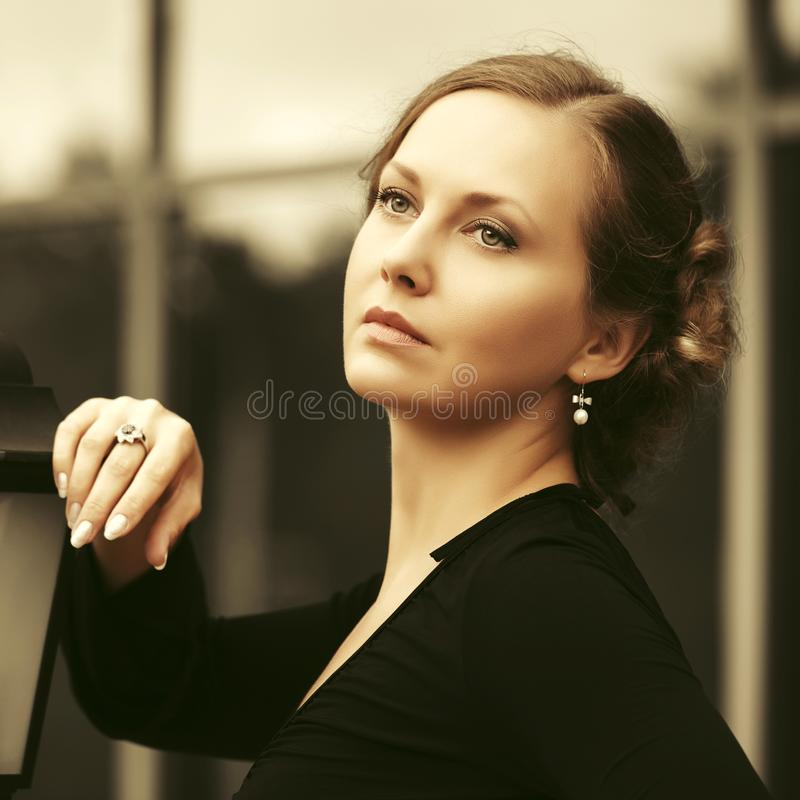 Droevige mooie maniervrouw die in zwarte blouse op stadsstraat lopen royalty-vrije stock foto