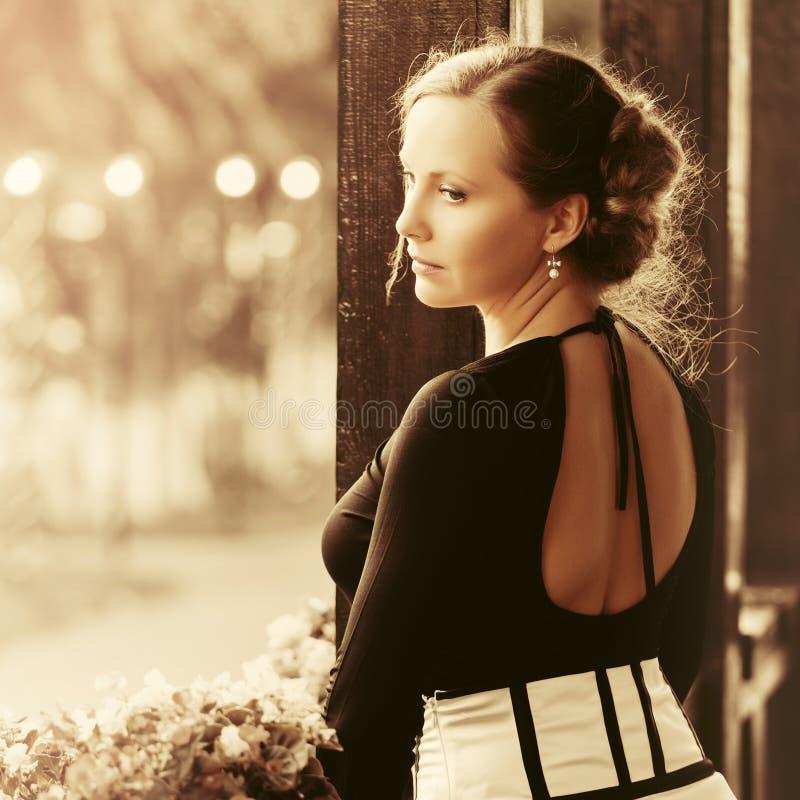 Droevige mooie maniervrouw met het haar die van broodjesupdo zich op portiek bevinden stock afbeeldingen