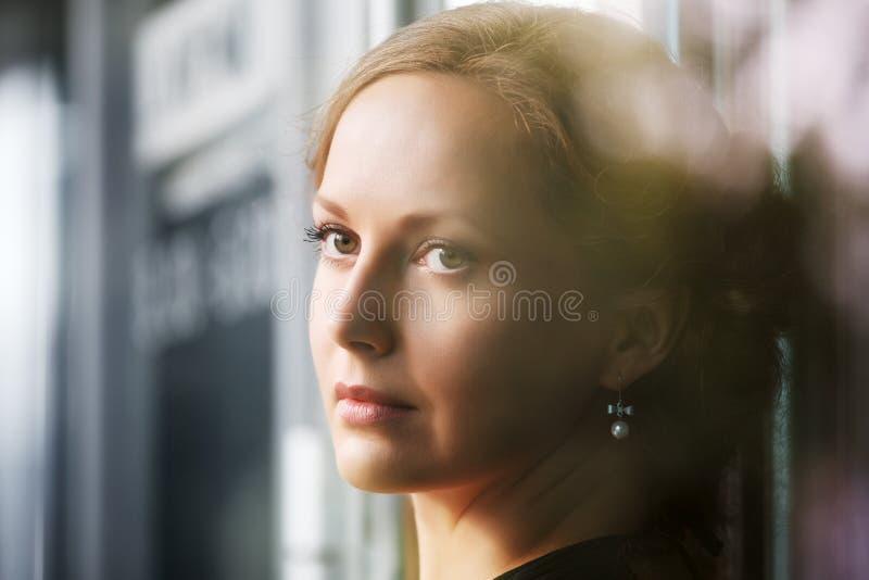 Droevige mooie vrouw die uit venster kijken royalty-vrije stock afbeeldingen
