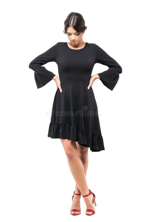 Droevige mooie vrouw die in zwarte kleding met handen op tailles neer kijken stock fotografie