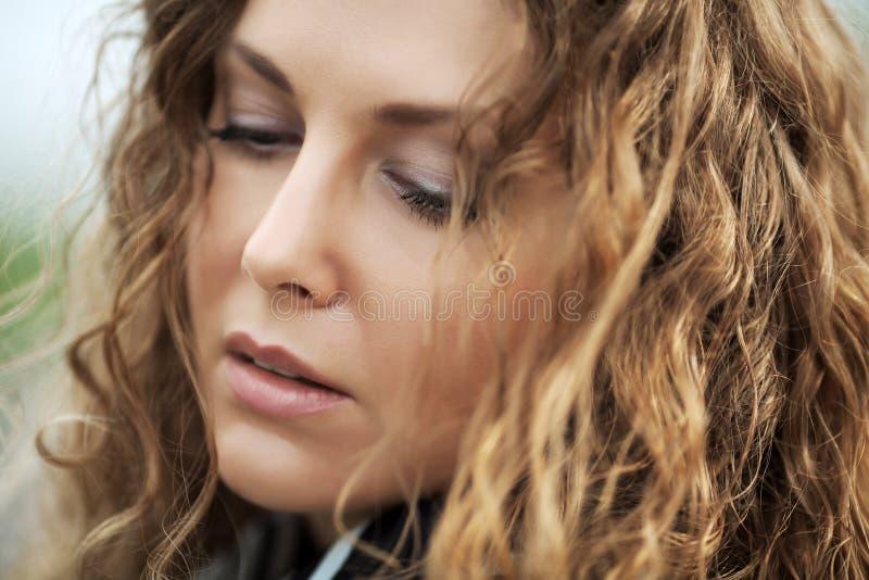 Droevige mooie vrouw met lange krullende haren royalty-vrije stock afbeeldingen