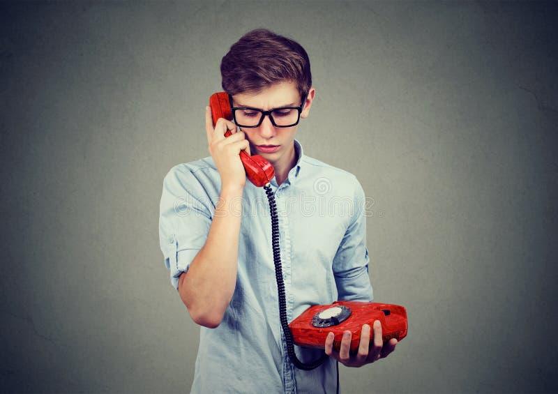 Droevige ongerust gemaakte tienermens die op een ouderwetse telefoon spreken stock foto