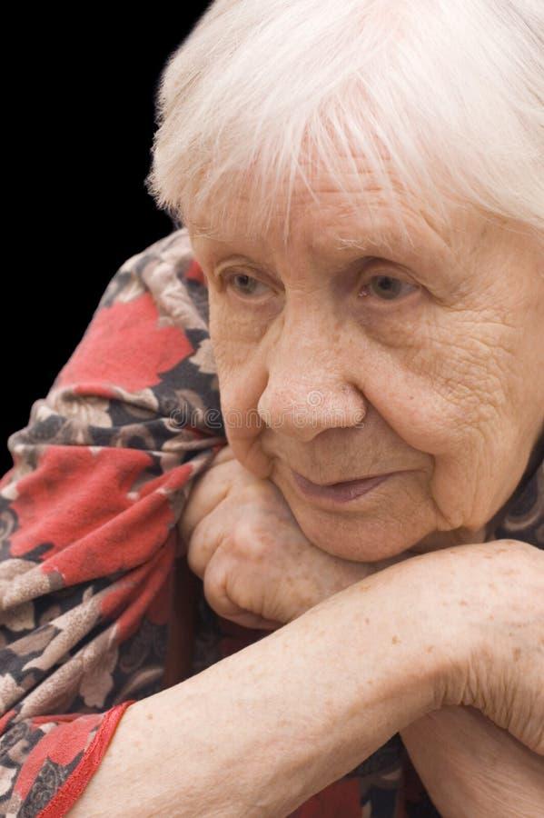 Droevige oude vrouw op de zwarte royalty-vrije stock foto