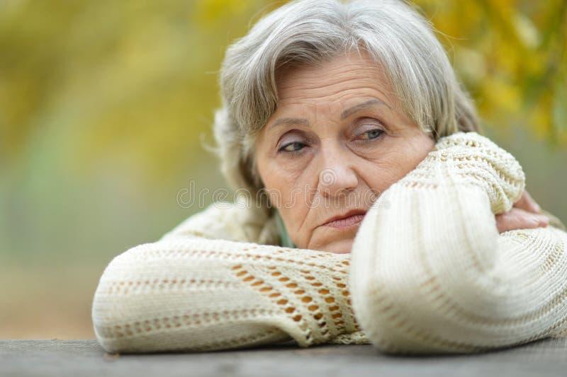 Droevige oude vrouw in park stock afbeelding