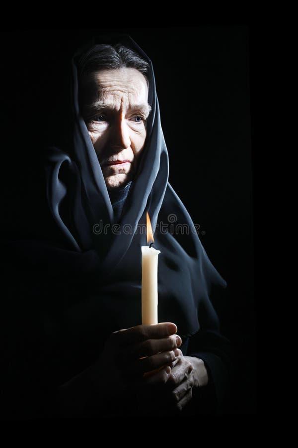 Droevige oude vrouwenoudste in verdriet met kaars royalty-vrije stock foto's