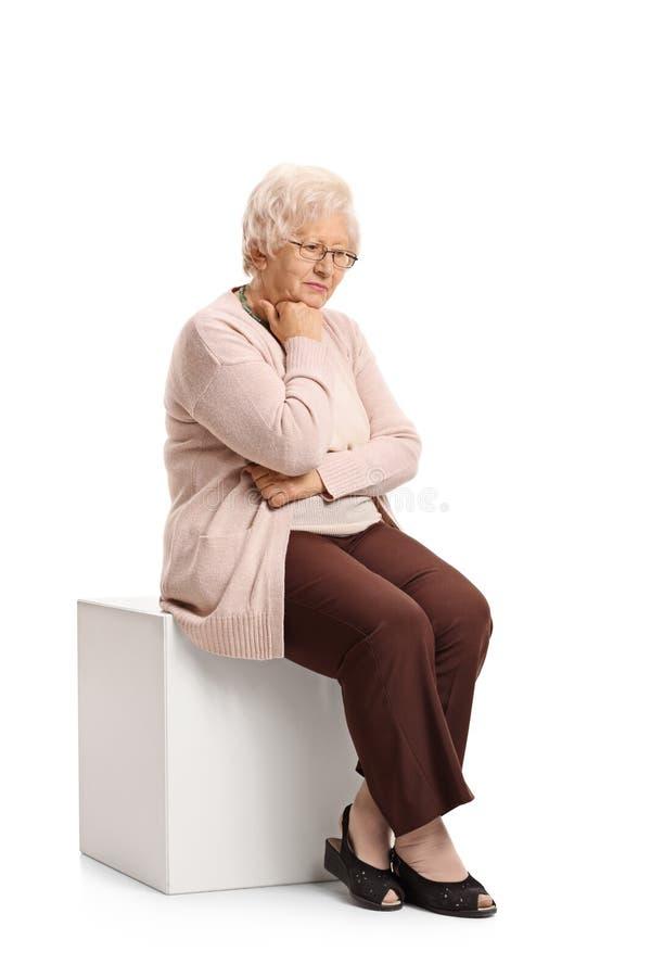 Droevige rijpe vrouwenzitting op een kubus royalty-vrije stock afbeeldingen