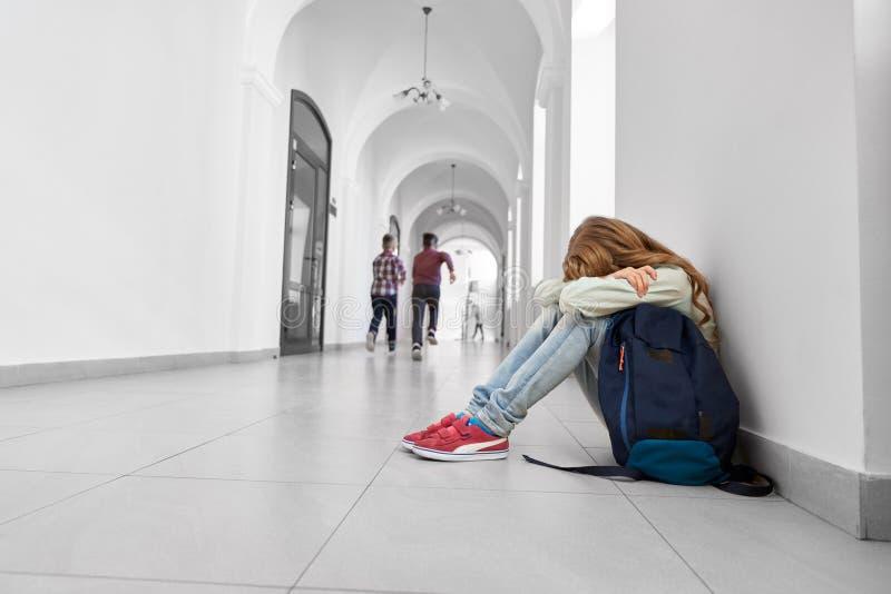 Droevige schoolmeisjezitting op vloer, het schreeuwen stock fotografie