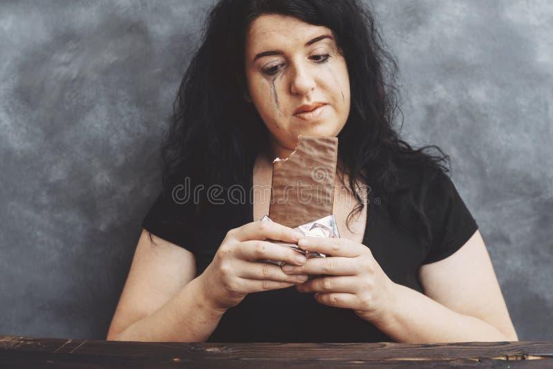Droevige schreeuwende jonge die vrouw van dieetbeperkingen wordt vermoeid die chocola eten royalty-vrije stock afbeelding