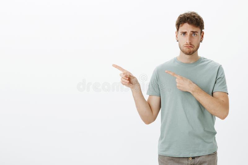Droevige sombere jonge mens in t-shirt, die verstoord teleurgesteld gezicht maken terwijl het richten links met wijsvingers, fron stock foto