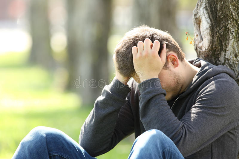 Droevige tiener die in een park betreuren stock fotografie
