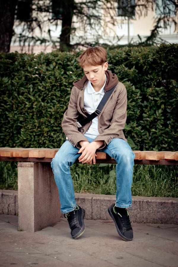 Droevige tienerzitting op bank in park stock foto