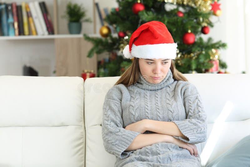 Droevige tienerzitting op een laag in Kerstmistijd thuis royalty-vrije stock fotografie