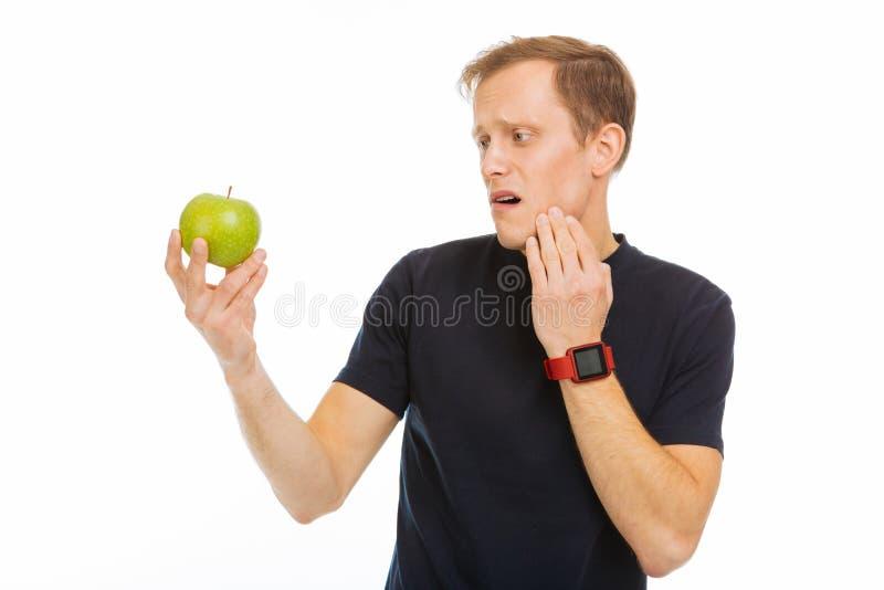Droevige trieste mens die de groene appel bekijken stock foto's
