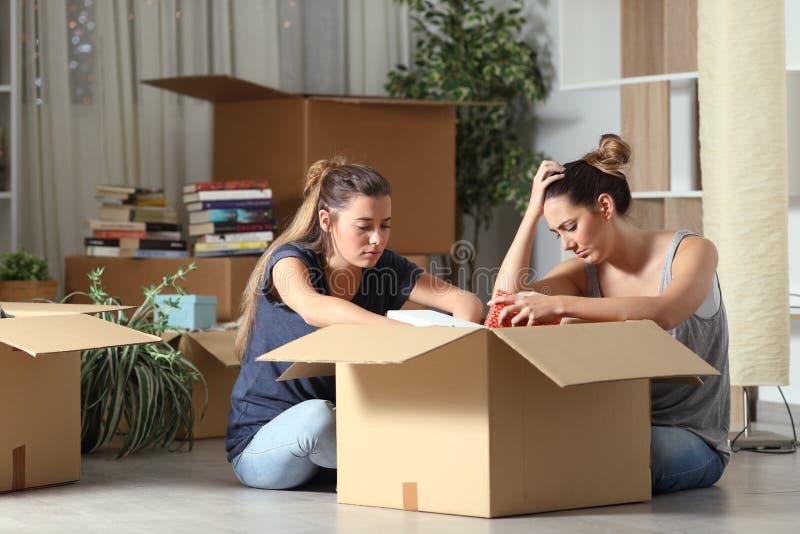 Droevige uitgezete kamergenoten die bezittingen in dozen doen die zich naar huis bewegen royalty-vrije stock foto