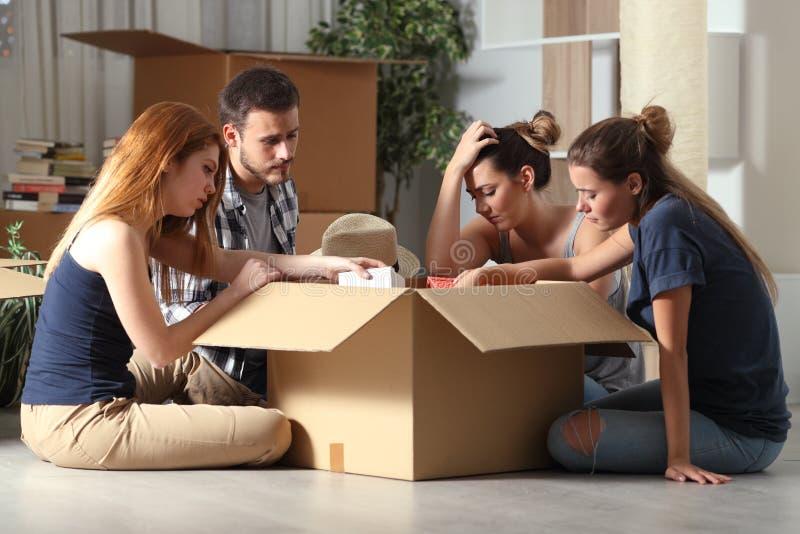 Droevige uitgezete kamergenoten die naar huis in dozen doende bezittingen bewegen stock afbeeldingen