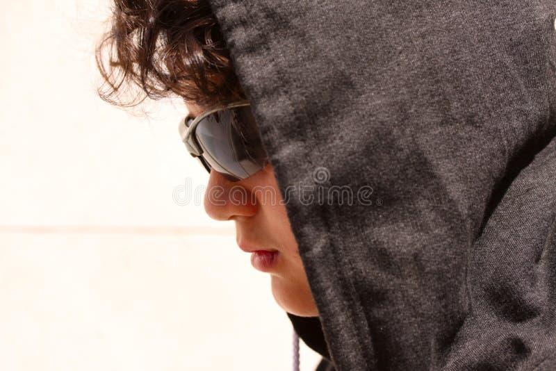 Droevige verontruste Spaanse 13 jaar oude Tiener die een hoodie en het donkere zonnebril stellen dragen openlucht - sluit omhoog royalty-vrije stock fotografie