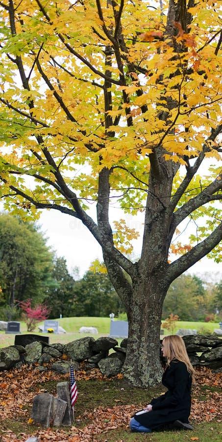 Droevige vrouw in begraafplaats stock foto