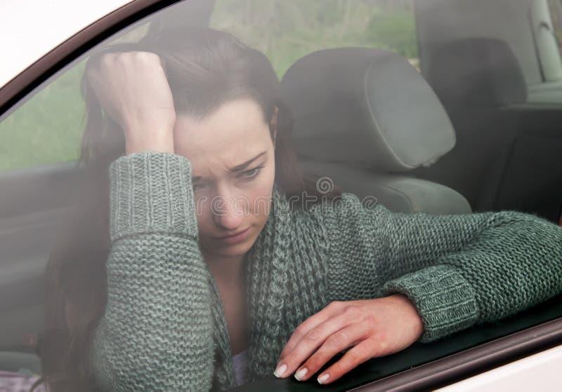 Droevige vrouw in de auto stock afbeeldingen
