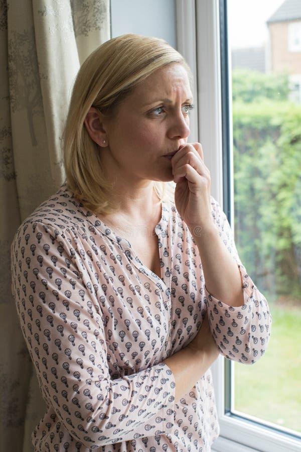 Droevige Vrouw die aan Pleinvrees lijden die uit Venster kijken stock afbeelding