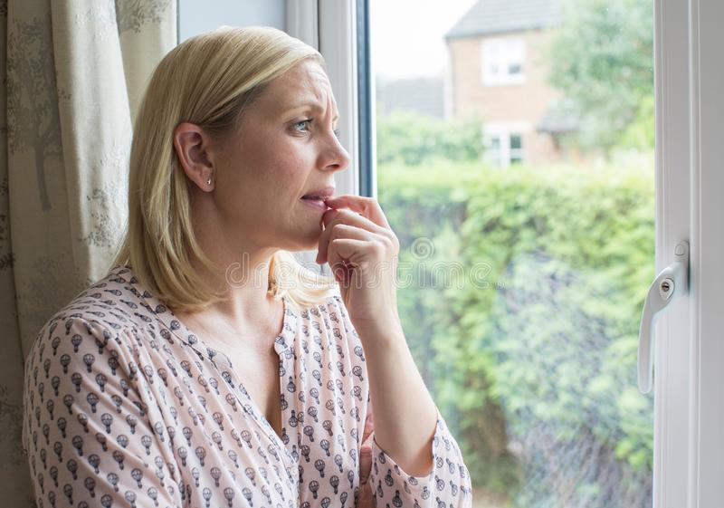 Droevige Vrouw die aan Pleinvrees lijden die uit Venster kijken royalty-vrije stock foto's