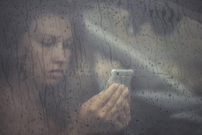 Droevige vrouw die in de mobiele telefoon kijken en bericht in het venster met regendaling lezen in de auto royalty-vrije stock fotografie