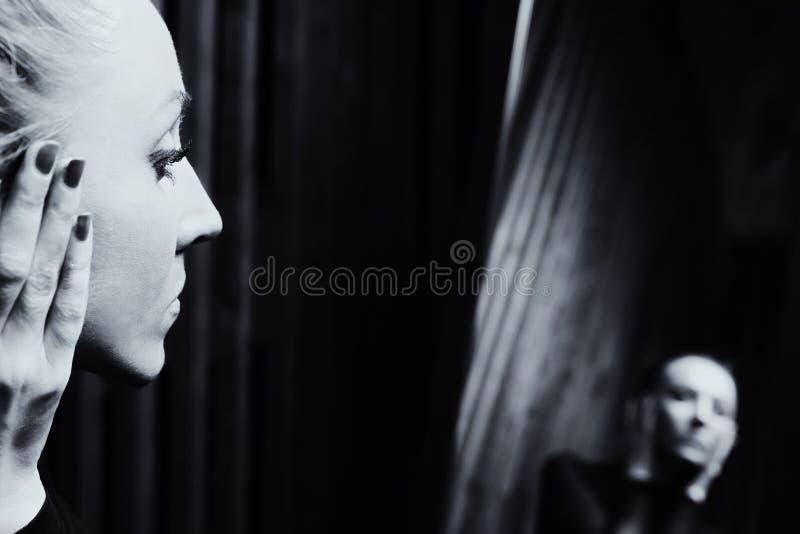Droevige vrouw die in de spiegel kijken stock afbeelding