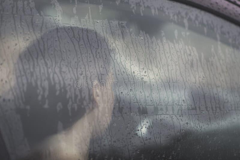 Droevige vrouw die door het venster met regendaling kijken in de auto Gezicht van jong wijfje achter regenautoraam stock afbeeldingen