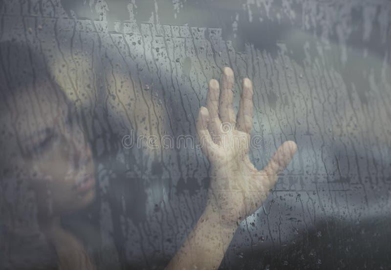 Droevige vrouw die door het venster met regendaling kijken in de auto Gezicht van jong wijfje achter regenautoraam royalty-vrije stock afbeelding