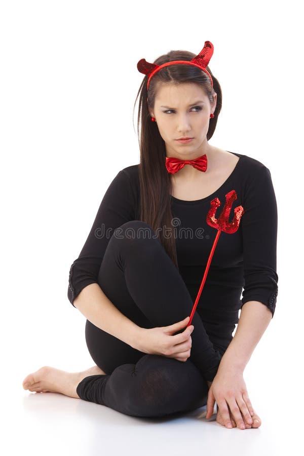 Droevige vrouw die duivelskostuum draagt stock afbeelding