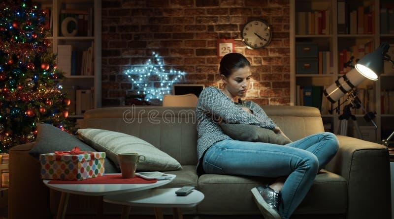 Droevige vrouw die eenzame Kerstmis hebben thuis stock fotografie