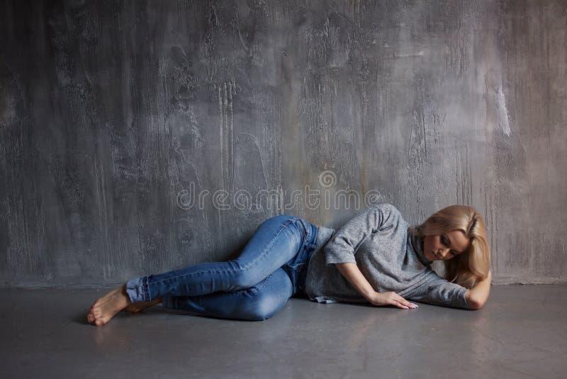 Droevige vrouw die op de vloer liggen Depressie en chronische moeheid Jong mooi blonde in een grijze sweater en jeans stock afbeeldingen