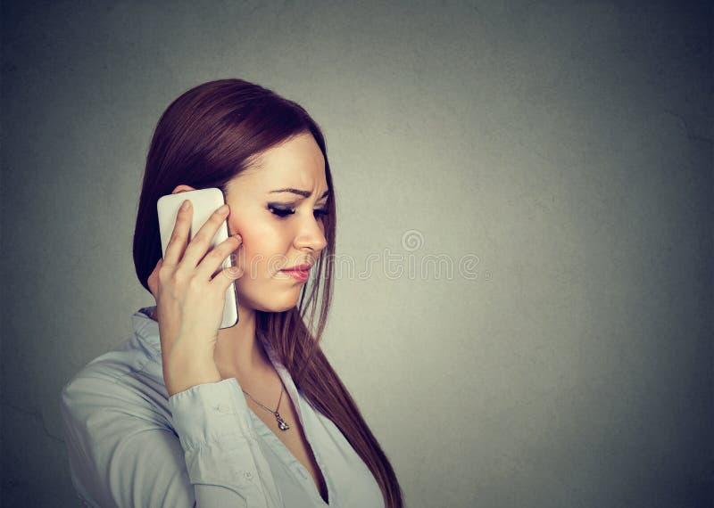 Droevige vrouw die op telefoon spreken stock fotografie