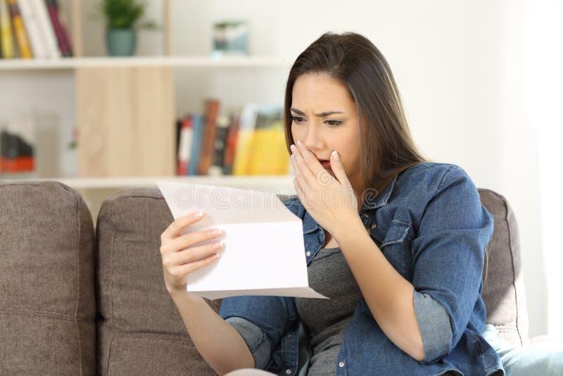 Droevige vrouw die slecht nieuws in een document brief lezen stock fotografie
