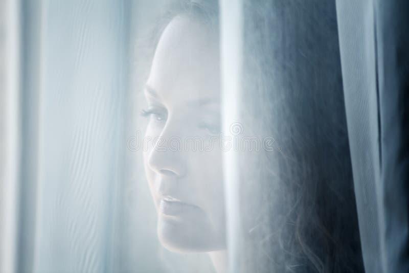 Droevige vrouw die uit het venster kijkt stock afbeeldingen