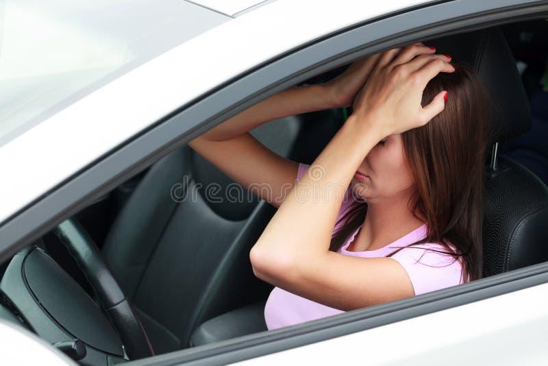 Droevige vrouw in een auto stock foto