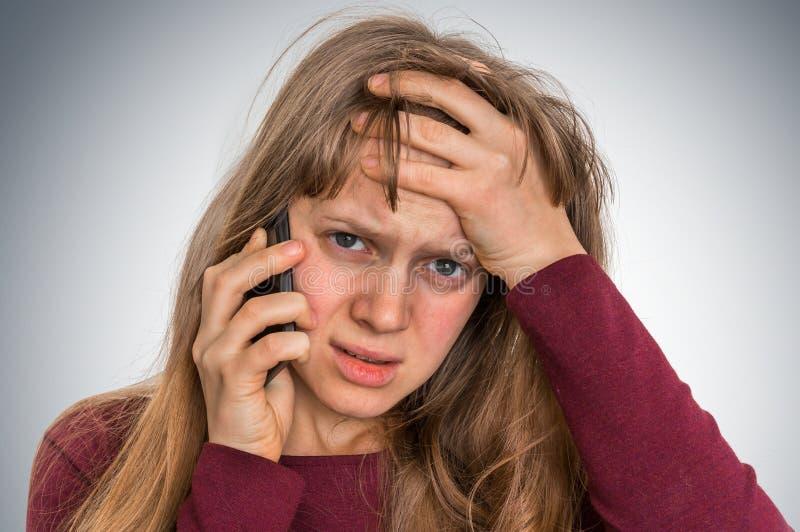 Droevige vrouw met mobiele telefoon - slecht nieuwsconcept royalty-vrije stock fotografie