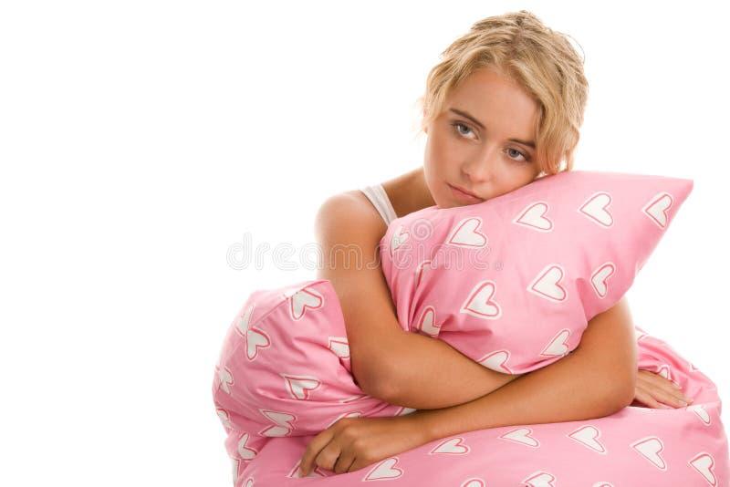 Droevige vrouw met roze hoofdkussen royalty-vrije stock afbeeldingen