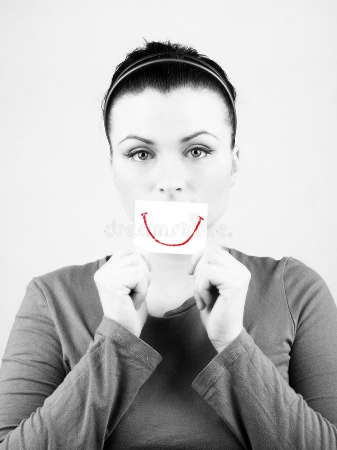 Droevige vrouw met valse glimlach. royalty-vrije stock afbeeldingen