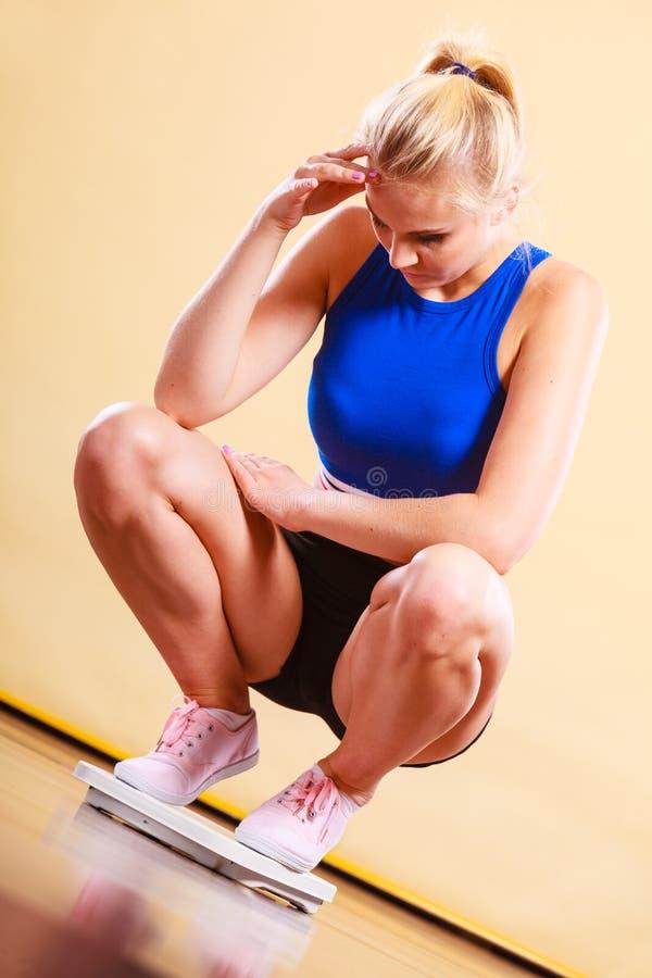 Droevige vrouw op gewichtsschaal stock foto