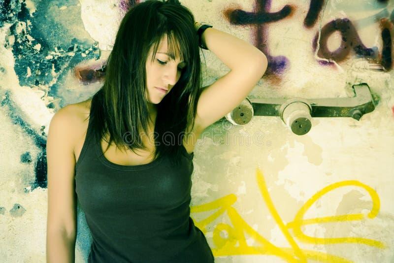 Droevige vrouw op vuile muur stock foto's
