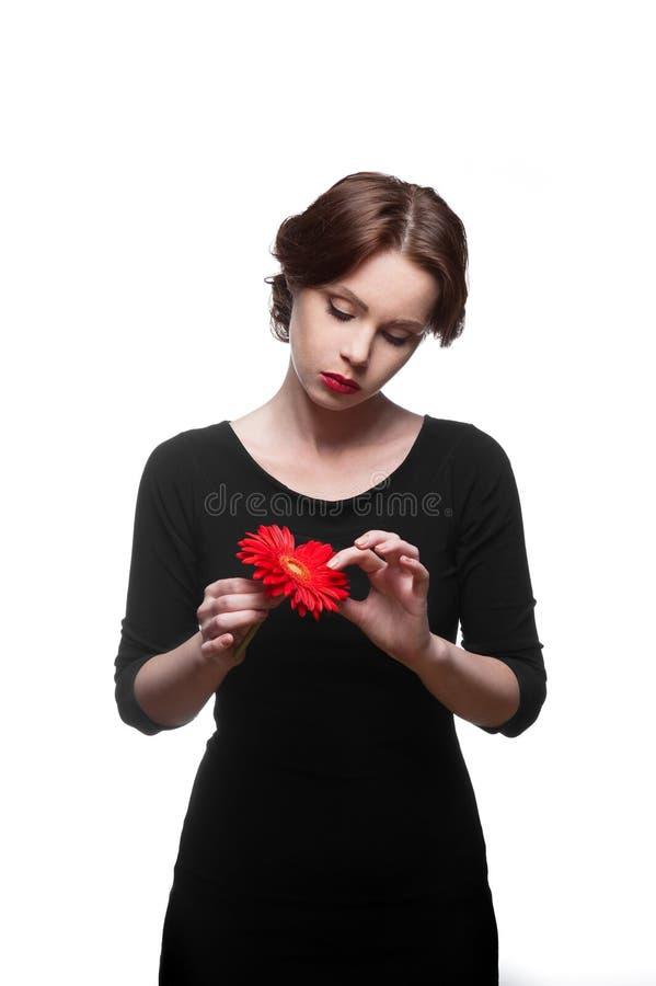 Droevige vrouw in zwarte kleding met rode bloem stock foto