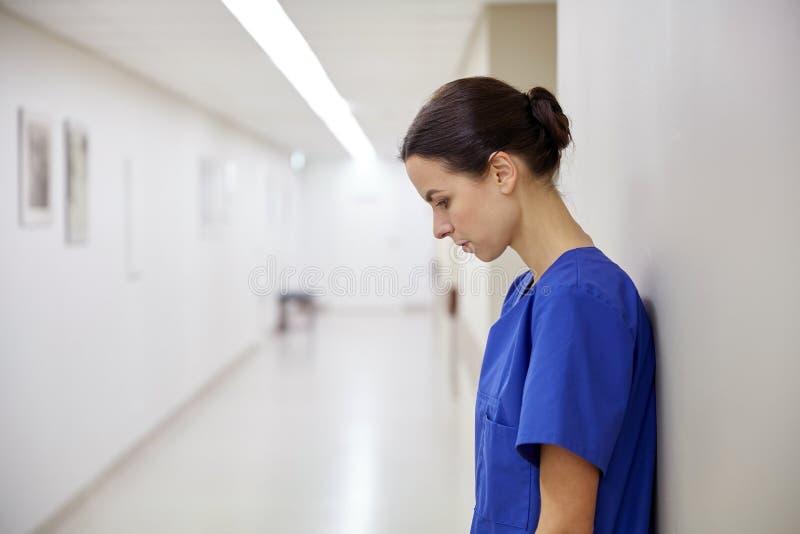 Droevige vrouwelijke verpleegster bij het ziekenhuisgang royalty-vrije stock foto